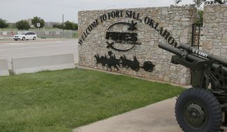 FILE - In this June 17, 2014 file photo, a vehicle drives by a sign at Scott Gate, one of the entrances to Fort Sill, in Fort Sill, Okla. The federal government has chosen Fort Sill, a military base in Oklahoma, as the location for a new temporary shelter to house migrant children. (AP Photo/Sue Ogrocki, File)