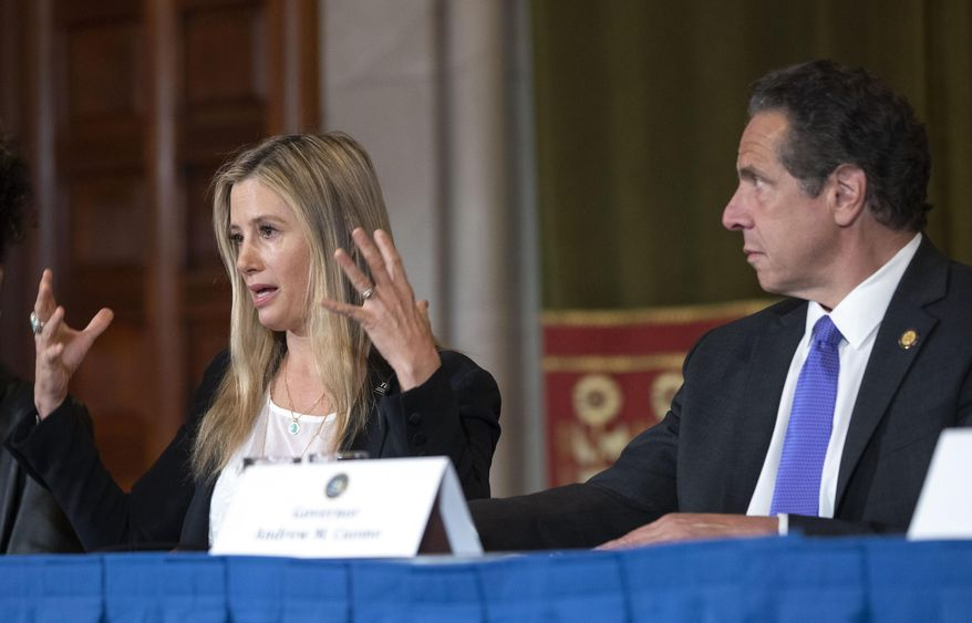 New York Gov. Andrew Cuomo, right, listens to Oscar-winning actress Mira Sorvino as she joined Times's Up advocates speaking out about sexual assault at the State Capitol in Albany, N.Y., Tuesday, June 12, 2019. Sorvino has revealed that she's a survivor of date rape in an attempt to lend her voice to a push for stronger sexual assault laws in New York. (Mike Groll/Office of Governor Andrew M. Cuomo via AP)