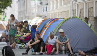Supporters of the former government camp outside the interior ministry in Chisinau, Moldova, Wednesday, June 12, 2019. Moldova's police chief on Wednesday dismissed six officers who publicly backed a rival government, reflecting a continuing power struggle that has heightened political tensions in the impoverished ex-Soviet nation.(AP Photo/Roveliu Buga)