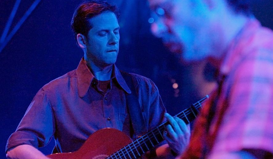 """FILE - In this July 24, 2007, file photo, U.S. musician Joey Burns and band Calexico perform on stage during the Blue Balls Festival in Lucerne, Switzerland. Reuniting on """"Years to Burn,"""" their first full-length project since 2005, Calexico and Iron & Wine remind audiences why they initially collaborated. Strong alone, the two bands are stronger together. (Sigi Tischler/Keystone via AP, File)"""