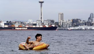 Carlos Moate floats on a beach toy just off-shore in Elliott Bay and in view of the Space Needle during an unusually warm day Wednesday, June 12, 2019, in Seattle. People in western Washington and Oregon are wilting under warmer than normal temperatures this week with highs into the mid-90s in some areas. (AP Photo/Elaine Thompson)