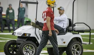 Quarterback Aaron Rodgers, left, walks past head coach Matt LaFleur during an NFL football practice in Green Bay, Wisc., Wednesday, June 12, 2019. LeFleur is recovering from a torn Achilles. (AP Photo/Mike Roemer)