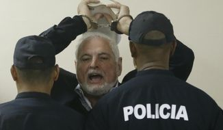 FILE - In this Nov. 19, 2018 file photo, Panama's former President President Ricardo Martinelli answers journalists questions as he raises his handcuffed hands, holding a book, while escorted by police to a hearing at the Supreme Court in Panama City. A Panamanian court has ordered on Wednesday, June 12, 2019, that former President Martinelli to be transferred from jail to house arrest. (AP Photo/Arnulfo Franco, File)