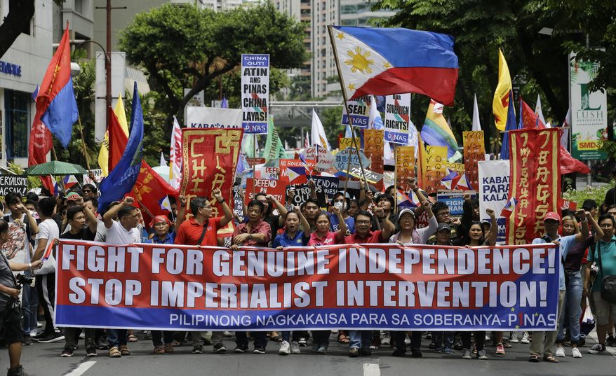 Protesters march towards the Chinese Consulate at the financial district of Makati, metropolitan Manila to mark Philippine Independence Day on Wednesday, June 12, 2019. The group said they condemn the administration of Philippine President Rodrigo Duterte for its alleged subservience to the dictates of U.S. and China. They also demanded that China must stop its continued occupation of the disputed South China Sea because it disrespects sovereign rights. (AP Photo/Aaron Favila)