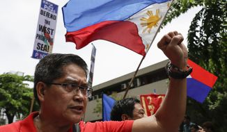 A protester raises his fist beside a national flag during a protest outside the Chinese Consulate in the financial district of Makati, metropolitan Manila, Philippines to mark Independence Day on Wednesday, June 12, 2019. The Philippine defense secretary says an anchored Filipino fishing boat has sunk in the disputed South China Sea after being hit by a suspected Chinese vessel which then abandoned the 22 Filipino crewmen. (AP Photo/Aaron Favila)