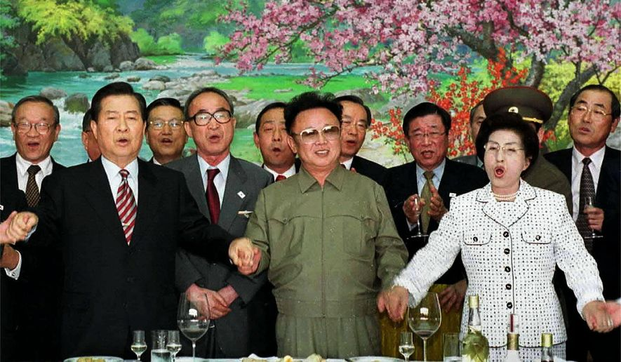 """FILE - In this June 15, 2000, file photo, from left in front row; former South Korean President Kim Dae-jung,  former North Korean leader Kim Jong Il, and former South Korean First Lady Lee Hee-ho, hold hands as they sing a song titled """"We Are Hoping For Reunification"""" at the Baekhwawon Guest House in Pyongyang during a luncheon party Thursday, June 15, 2000. (AP Photo/KOREA POOL/YONHAP, File)"""