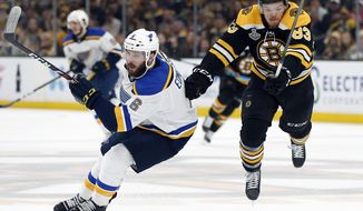 St. Louis Blues' Joel Edmundson (6) sends Boston Bruins' Karson Kuhlman (83) airborne during the second period in Game 7 of the NHL hockey Stanley Cup Final, Wednesday, June 12, 2019, in Boston. (AP Photo/Michael Dwyer)