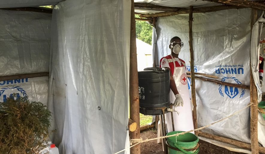 This photo taken Monday, June 10, 2019, and released by the International Rescue Committee (IRC), shows an Ebola screening checkpoint where people crossing from Congo go through foot and hand washing with a chlorine solution and have their temperature taken, at the Bunagana border crossing with Congo, in western Uganda. (Ben Wise/International Rescue Committee via AP)