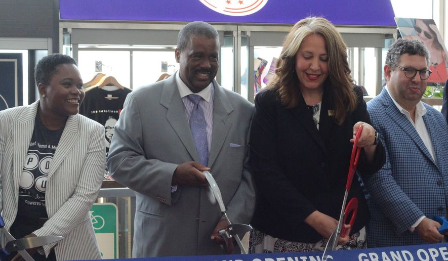 Cutting the ceremonial ribbon on Thursday at the Made in DC kiosk at Ronald Reagan National Airport were (from left) Pop Up Collaborative founder Rahama Wright; Metropolitan Washington Airport Authority Board of Directors chairman Warner H. Session; and Kristi Whitfield, Made in DC founder and director of the D.C. Department of Small and Local Business Development. (Emily Ketterer/The Washington Times)