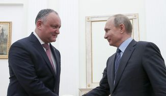 Russian President Vladimir Putin, right, shakes hands with his Moldovan counterpart Igor Dodon during a meeting at the Kremlin in Moscow, Russia, Wednesday, Jan. 30, 2019. (Maxim Shemetov/Pool Photo via AP) **FILE**