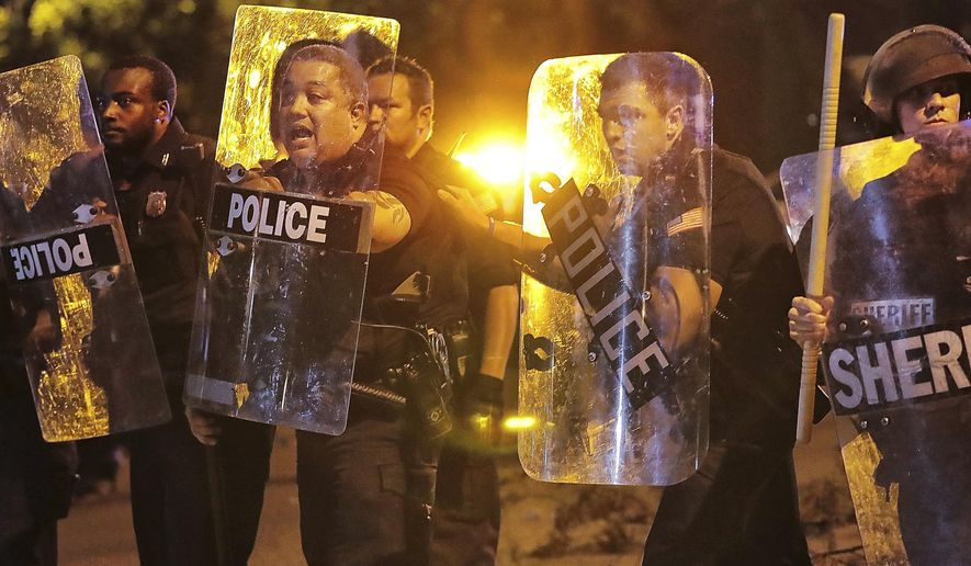 Memphis police brace against the crowd as protesters take to the streets of the Frayser community in anger against the shooting a youth by U.S. Marshals earlier in the evening, Wednesday, June 12, 2019, in Memphis, Tenn. (Jim Weber/Daily Memphian via AP)