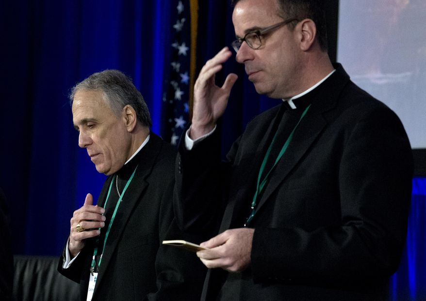 Cardinal Daniel DiNardo, left, of the Archdiocese of Galveston-Houston, president of the United States Conference of Catholic Bishops, accompanied by the Rev. J. Brian Bransfield, participates in a morning prayer, during the United States Conference of Catholic Bishops (USCCB), 2019 Spring meetings in Baltimore, Tuesday, Jun 11, 2019. (AP Photo/Jose Luis Magana)