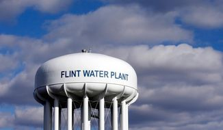 FILE - In this March 21, 2016 file photo, the Flint Water Plant water tower is seen in Flint, Mich. Prosecutors dropped all criminal charges Thursday, June 13, 2019, against eight people in the Flint water scandal and pledged to start the investigation from scratch. The defendants include Michigan's former health director, Nick Lyon, who was charged with involuntary manslaughter. He was accused of failing to timely alert the public about an outbreak of Legionnaires' disease that occurred in 2014-15 when Flint was drawing improperly treated water from the Flint River.  (AP Photo/Carlos Osorio, File)