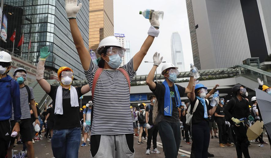 In this June 12, 2019, photo, demonstrators raise their hands near the Legislative Council in Hong Kong. (AP Photo/Kin Cheung, File)