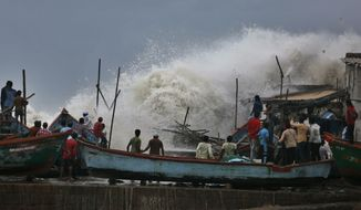 A waves crashes as people stand on boats on the Arabian Sea coast in Veraval, Gujarat, India, Wednesday, June 12, 2019. Indian authorities evacuated tens of thousands of people on Wednesday as a severe cyclone in the Arabian Sea approached the western state of Gujarat, lashing the coast with high winds and heavy rainfall. (AP Photo/Ajit Solanki)
