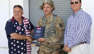 NFAA President Bruce Cul, left, and Aaron Ness of First Dakota National Bank present Captain B.J. Poore, center, of the South Dakota National Guard's 155th Vertical Engineer Company with a plaque Wednesday, June 12, 2019, in recognition of the guard's continued help at the NFAA Easton Yankton Archery Complex.  (Kelly Hertz/Yankton Press & Dakotan via AP)