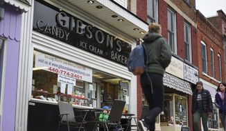 In this Nov. 22, 2017, file photo, pedestrians pass the storefront of Gibson's Food Mart & Bakery in Oberlin, Ohio. A jury has awarded $11 million to a father and son who claimed Ohio's Oberlin College and an administrator hurt their business and libeled them during a dispute that triggered protests and allegations of racism following a shoplifting incident. (AP Photo/Dake Kang, File) ** FILE **