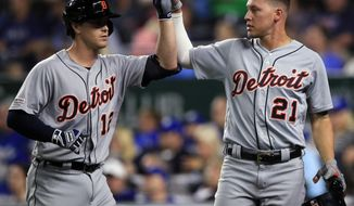 Detroit Tigers' Brandon Dixon (12) and JaCoby Jones (21) celebrate during the eighth inning of the team's baseball game against the Kansas City Royals at Kauffman Stadium in Kansas City, Mo., Wednesday, June 12, 2019. Dixon drove in Jones with a sacrifice fly. (AP Photo/Orlin Wagner)