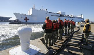 In this Dec. 18, 2018, photo, line handlers wait as the US Navy Hospital Ship USNS Comfort arrives pier side at Naval Station Norfolk, in Norfolk , Va., after an 11-week medical support mission to South and Central America. The USNS Comfort begins on Friday, June 14, 2019, a five-month medical mission that will include 11 countries impacted by the flow of Venezuelan migration. The ship will depart Friday from Norfolk, Virginia (AP Photo/Steve Helber) **FILE**