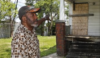 In a photo from Tuesday, June 11, 2019, Stanley Allen talks about an empty house next to his in Detroit. Hundreds of vacant houses in Detroit are being boarded up as the city responds to safety concerns following the arrest of a man suspected of killing at least three women. Since Friday, plywood has been nailed across doors and lower-level windows on more than 120 houses just south of the city's northern limits. (AP Photo/Carlos Osorio)