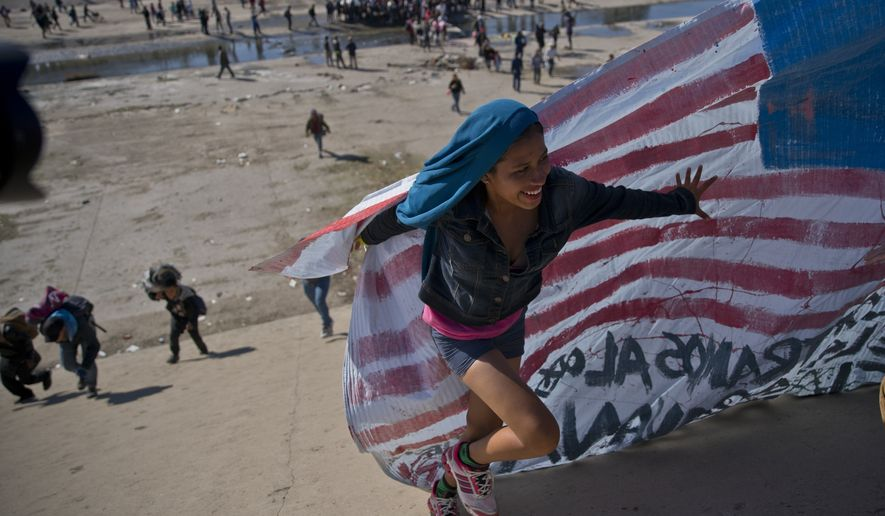 FILE - In this Nov. 25, 2018 file photo, a migrant woman helps carry a handmade U.S. flag up the riverbank at the Mexico-U.S. border after getting past Mexican police at the Chaparral border crossing in Tijuana, Mexico, as a group of migrants tries to reach the U.S.  Activists, officials and social workers in Central America were staggered by the idea that U.S. President Donald Trump thinks he will help reduce immigration, by cutting off nearly $500 million in aid to Honduras, Guatemala and El Salvador; exactly the opposite will happen, they say. (AP Photo/Ramon Espinosa, File)