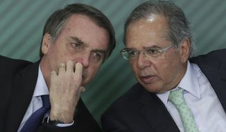 FILE - In this April 8, 2019 file photo, Brazil's President Jair Bolsonaro, left, talks with Economy Minister Paulo Guedes, at the Planalto Presidential Palace, in Brasilia, Brazil. The South American country kicked off a general strike Friday, June 14, that is likely to paralyze major cities across Brazil. The nationwide strike is the first since the arrival of far-right President Jair Bolsonaro on Jan. 1. (AP Photo/Eraldo Peres, File)