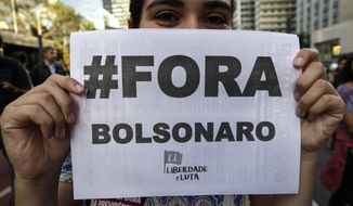 """A demonstrator shows her Portuguese message """"Get out Bolsonaro"""" during a general strike in Sao Paulo, Brazil, Friday, June 14, 2019. The strike is the first of its kind since President Jair Bolsonaro took office in January. (AP Photo/Suamy Beydoun)"""