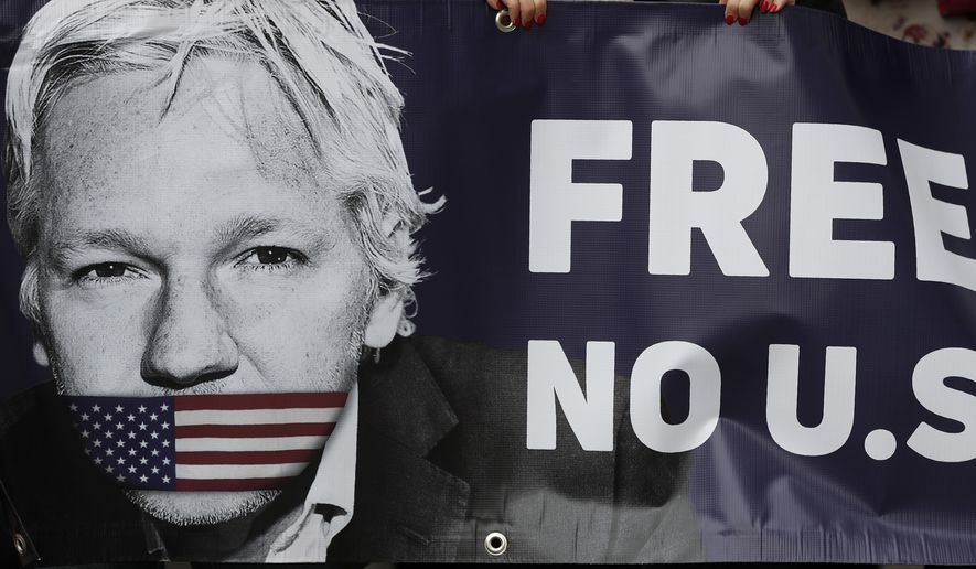 Assange supporters hold a banner to protest outside Westminster Magistrates Court in London, Friday, June 14, 2019. WikiLeaks founder Julian Assange is expected to appear via a video link at court Friday, as he continues his fight against extradition to the United States, where he faces prosecution under the Espionage Act. (AP Photo/Frank Augstein)