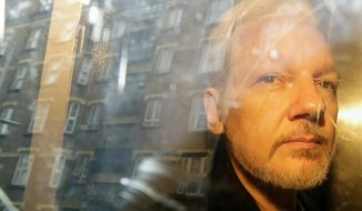 In this file photo dated Wednesday, May 1, 2019, buildings are reflected in the window as WikiLeaks founder Julian Assange is taken from court, where he appeared on charges of jumping British bail seven years ago, in London.  47-year old Assange is expected to appear via a video link at court Friday, June 14, 2019, as he continues his fight against extradition to the United States, where he faces prosecution under the Espionage Act.  (AP Photo/Matt Dunham, FILE)