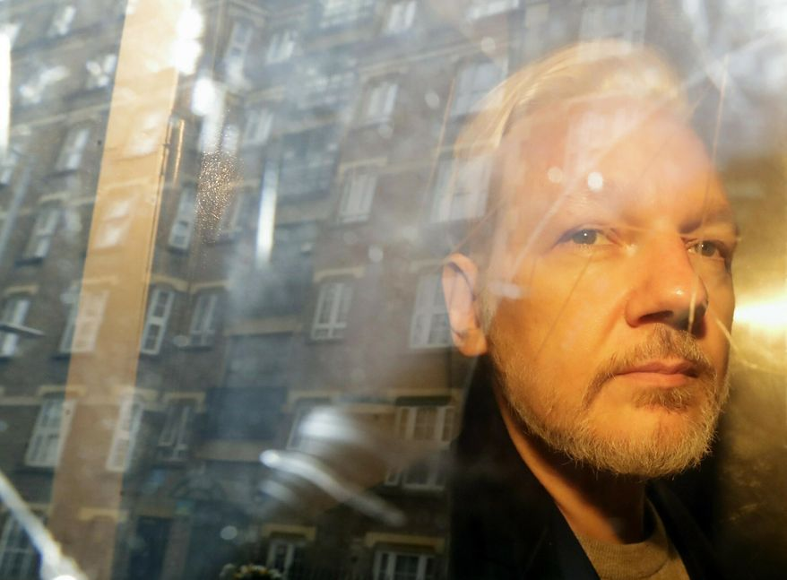 In this file photo dated Wednesday, May 1, 2019, buildings are reflected in the window as WikiLeaks founder Julian Assange is taken from court, where he appeared on charges of jumping British bail seven years ago, in London. (AP Photo/Matt Dunham, File)