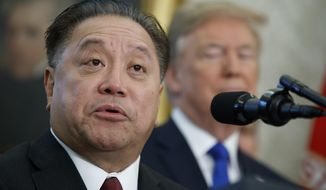 "FILE - In this Nov. 2, 2017, file photo, Broadcom CEO Hock Tan speaks as President Donald Trump listens during an event to announce the company is moving its global headquarters to the United States, in the Oval Office of the White House, in Washington. Broadcom's shares fell on Friday, June 14, 2019, along with those of other chipmakers, after the company lowered revenue guidance for the rest of the year due to trade tensions and a ""broad-based"" slowdown in general. (AP Photo/Evan Vucci, File)"