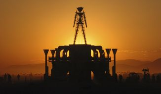 """FILE - In this Sept. 2, 2006 file photo, """"The Man,"""" a stick figured symbol of the Burning Man art festival, is silhouetted against a morning sunrise in Nevada's Black Rock Desert. The U.S. Bureau of Land Management is recommending attendance be capped at existing levels for the next 10 years at the annual Burning Man counter-culture festival in the desert 100 miles north of Reno. Burning Man organizers had proposed raising the current 80,000 limit as high as 100,000 in coming years. (AP Photo/Ron Lewis, File)"""