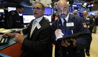 FILE - In this June 6, 2019, file photo specialist Anthony Rinaldi, left, and trader Fred DeMarco work on the floor of the New York Stock Exchange. The U.S. stock market opens at 9:30 a.m. EDT on Friday, June 14. (AP Photo/Richard Drew, File)