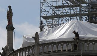 FILE - In this April 26, 2019 file photo, a worker checks the waterproof tarps on Notre Dame cathedral in Paris. The billionaire French donors that publicly promised flashy donations totalling hundreds of millions to restore Notre Dame, have not yet paid a penny toward the restoration of the French national monument, according to church and business officials. Instead, it's mainly American citizens that have footed the bills and paid salaries for the up to 150 workers employed by the cathedral since the April 15 fire. (AP Photo/Michel Euler, File)