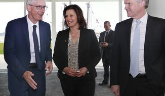 Wisconsin Gov. Tony Evers, left, Michigan Gov. Gretchen Whitmer and Ontario's Minister of the Environment, Conservation and Parks, Rod Phillips, leave a press conference after sharing highlights of their 2019 Leadership Summit at the Discovery World, Friday, June 14, 2019 in Milwaukee, Wis. (Angela Peterson/Milwaukee Journal-Sentinel via AP)