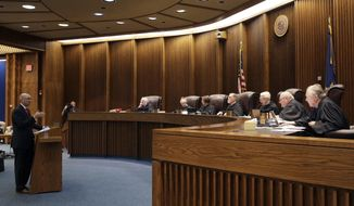 FILE - In this May 9, 2019 photo, State of Kansas attorney Toby Crouse, left, presents his case before the Kansas Supreme Court during oral arguments in a school funding case in Topeka, Kan. Kansas' highest court has signed off on an increase in spending on public schools that the Democratic governor pushed through the Republican-controlled Legislature. But the justices declined in their ruling Friday to close the protracted education funding lawsuit that prompted their decision. The school finance law boosted funding roughly $90 million a year. The court said it wants to ensure that the state keeps its funding promises. (AP Photo/Charlie Riedel, File)