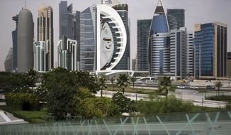 FILE - In this May 5, 2018, file photo, a giant image of the Emir of Qatar Sheikh Tamim bin Hamad Al Thani, adorns a tower in Doha, Qatar.  The highest U.N. court has rejected a request by the United Arab Emirates for interim measures to be imposed on Qatar in a racial discrimination dispute. The case centers on the boycott of Qatar by Bahrain, Egypt, the UAE and Saudi Arabia, which were angry at Qatar's support for Islamists.Qatar filed a case last year against UAE alleging that the boycott breaches an anti-discrimination convention. Judges issued an interim order that Qatari families separated by the UAE boycott must be allowed to reunite and Qatari students should be allowed to complete their education in the UAE.   (AP Photo/Kamran Jebreili, File)