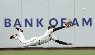 San Francisco Giants left fielder Mike Yastrzemski dives to catch a fly ball hit by Milwaukee Brewers' Yasmani Grandal for the final out of the ninth inning of a baseball game in San Francisco, Saturday, June 15, 2019. (AP Photo/Jeff Chiu)