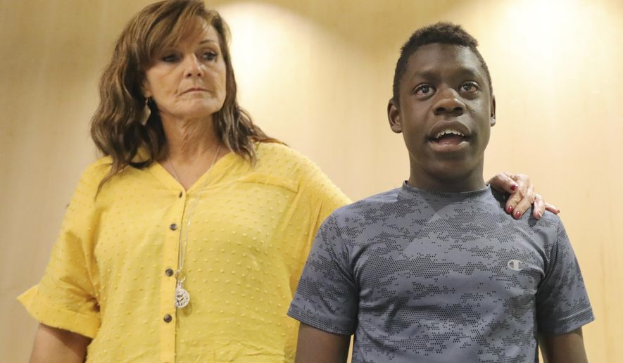 FILE - In this June 7, 2019 file photo, Jerri Hrubes stands next to her son DJ during a news conference Friday, June 7, 2019, in Salt Lake City.  About 100 protesters gathered outside a police agency, Friday, June 14,  to demand an officer who pulled his gun on 10-year-old  Hrubes last week be fired. The officer's actions drew criticism after Jerri Hrubes said the white police officer pulled his gun on her son, DJ, who is black, while he was playing on his grandmother's front lawn on June 6.  (AP Photo/Rick Bowmer)