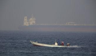 A fishing boat speeds past an oil tanker in the distance in Fujairah, United Arab Emirates, Saturday, June 15, 2019. The Kokuka Courageous, one of two oil tankers targeted in an apparent attack in the Gulf of Oman, was brought to the United Arab Emirates' eastern coast Saturday. (AP Photo/Jon Gambrell)