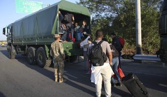 Venezuelan migrants climb-up on to Peruvian Army truck to be transported on the Pan-American Highway, after stricter entry requirements went into effect, in Tumbes, Peru, Saturday, June 15, 2019. With its relatively stable economy and flexible immigration laws, Peru has become a main destination for millions of Venezuelans escaping hyperinflation, medical shortages and political repression at home. (AP Photo/Martin Mejia)
