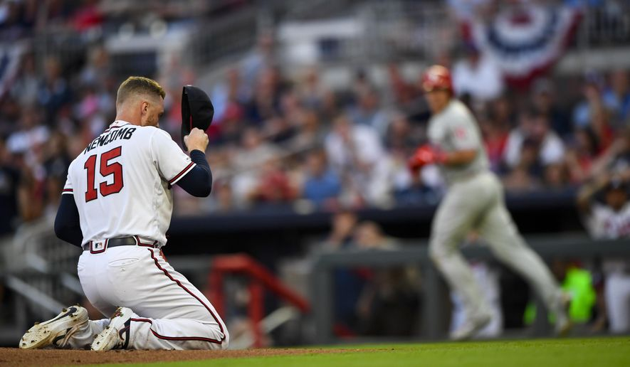 Atlanta Braves pitcher Sean Newcomb (15) goes to his knees after being hit in the head with a line drive by Philadelphia Phillies' J.T. Realmuto, right, as Realmuto makes his way to base on a ground-rule double and injury delay during the third inning of a baseball game Saturday, June 15, 2019, in Atlanta. Newcombe came out of the game. (AP Photo/John Amis)