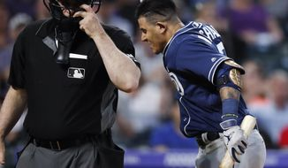 San Diego Padres' Manny Machado, right, throws down his helmet as he yells at home plate umpire Bill Welke, who had called Machado out on strikes during the fifth inning of the team's baseball game against the Colorado Rockies on Saturday, June 15, 2019, in Denver. (AP Photo/David Zalubowski)