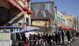 FILE - In this Nov. 3, 2017, file photo, residents walk through a security checkpoint into the Hotan Bazaar where a screen shows Chinese President Xi Jinping in Hotan in western China's Xinjiang region. China says the U.N.'s counterterrorism chief visited Xinjiang last week despite protests from the U.S. and a rights group that the trip would be inappropriate in light of the human rights conditions in the far west region. (AP Photo/Ng Han Guan, File)