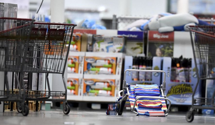 Scattered shopping carts and a flipped over beach chair lays on the ground following a shooting inside a Costco in Corona, Calif.,  Friday, June 14, 2019.  A gunman opened fire inside the store during an argument,  killing a man, wounding two other people and sparking a stampede of terrified shoppers before he was taken into custody, police said. The man involved in the argument was killed and two other people were wounded, Corona police Lt. Jeff Edwards said.  (Will Lester/Inland Valley Daily Bulletin/SCNG via AP)