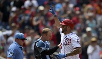 Washington Nationals' Matt Adams, right, celebrates his three-run home run as Arizona Diamondbacks catcher Caleb Joseph, center, and umpire home plate Sean Barber (29) look on during the third inning of a baseball game Sunday, June 16, 2019, in Washington. (AP Photo/Nick Wass)
