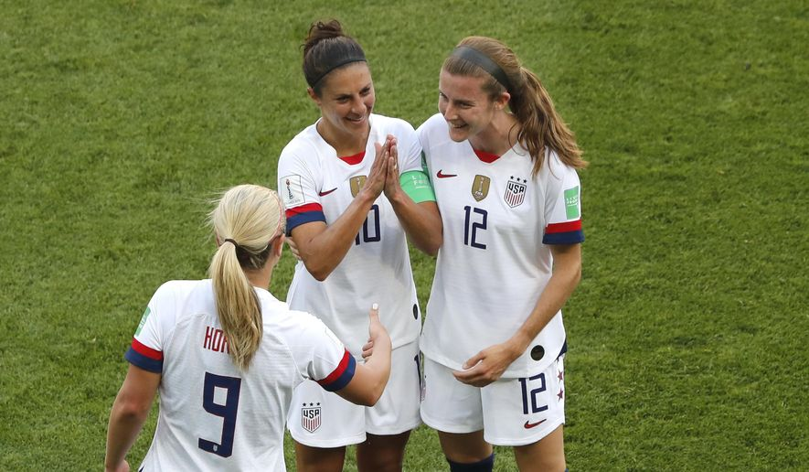 United States' Carli Lloyd , center, celebrates with Lindsey Horan and Tierna Davidson, right, after scoring the opening goal during the Women's World Cup Group F soccer match between the United States and Chile at the Parc des Princes in Paris, Sunday, June 16, 2019. (AP Photo/Thibault Camus)