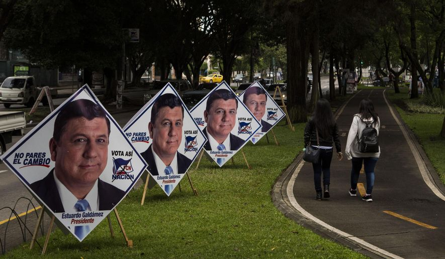 Women walk on the pedestrian path next to campaign posters promoting the ruling party presidential candidate Estuardo Galdamez, in Guatemala City, Saturday, June 15, 2019. The road to Sunday's presidential election in Guatemala has been a chaotic flurry of court rulings and shenanigans, illegal party-switching and allegations of malfeasance that torpedoed the candidacies of two of the top three candidates. (AP Photo/Oliver de Ros)