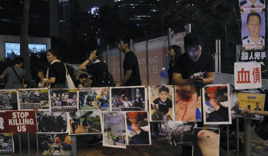 Protesters gather near photos of other protesters injured during Wednesday's violent protest, as well as photos of police commander they claimed had authorized the use of aggressive tactics, in Hong Kong on Sunday, June 16, 2019. Hong Kong citizens marched for hours Sunday in a massive protest that drew a late-in-the-day apology from the city's top leader for her handling of legislation that has stoked fears of expanding control from Beijing in this former British colony. (AP Photo/Kin Cheung)