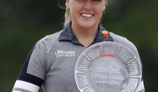 Brooke Henderson, of Canada, holds the championship trophy after winning the Meijer LPA Classic golf tournament, Sunday, June 16, 2019, in Grand Rapids, Mich. (AP Photo/Al Goldis)